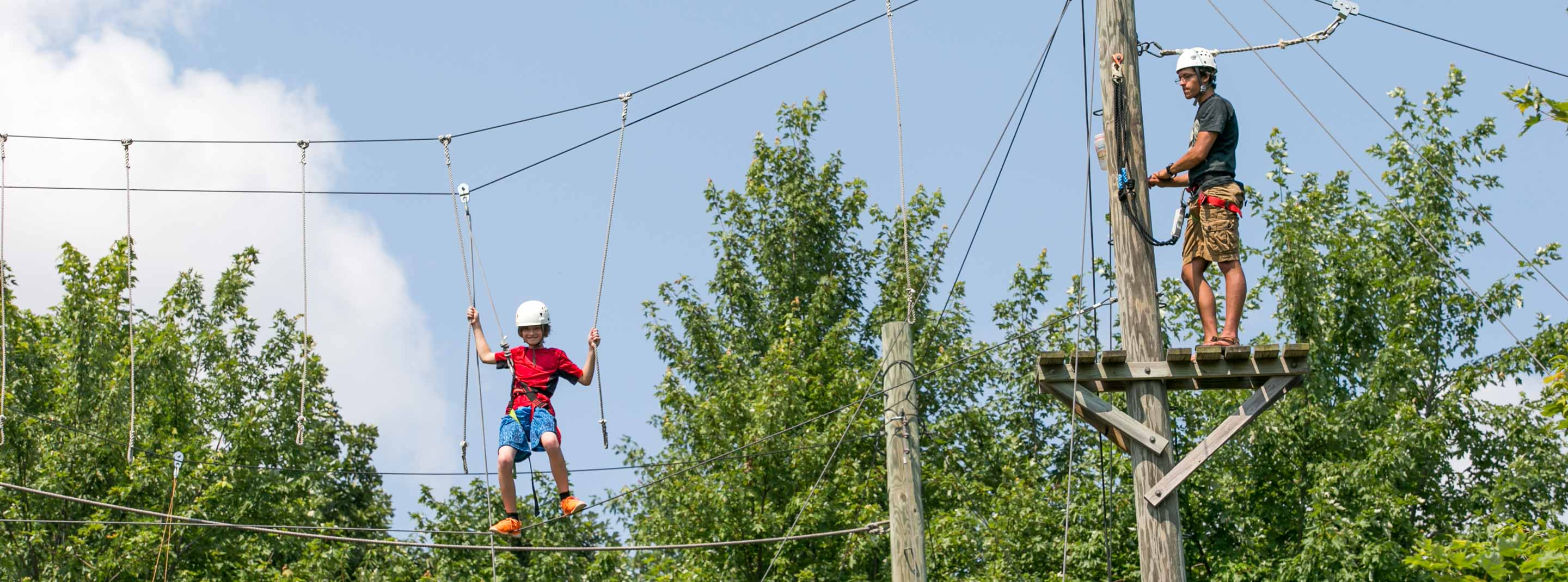 Staff and camper on high ropes course